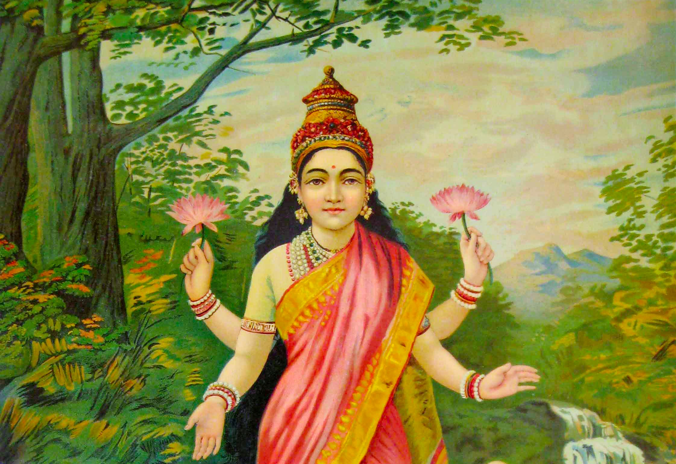 Lakshmi, a goddess stands on a lotus flower in a body of water. She wears a pink sari and has four arms, two of which are holding flowers. Her gaze rests calmly on the viewer.