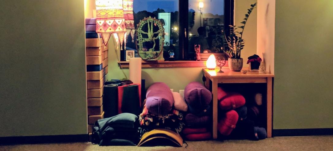 Bolsters, mats, blocks. Warm lighting.